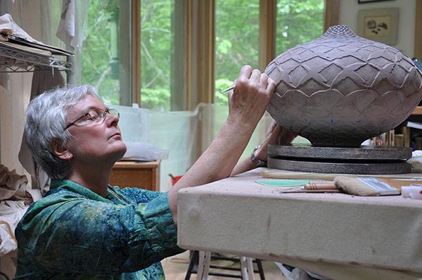 Photo of Judith Ernst working in her studio